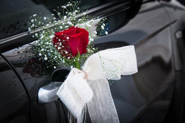 L'ornamento di una rosa rossa con fiocco bianco decora piacevolmente il manico d'argento dell'auto nuziale nera. cerimonia concetto di dettaglio