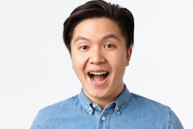 Ortodonzia, cure odontoiatriche e concetto di stomatologia. primo piano di un uomo asiatico entusiasta e sorpreso che sembra divertito e sorridente, che mostra le parentesi graffe dei denti, in piedi su uno sfondo bianco.