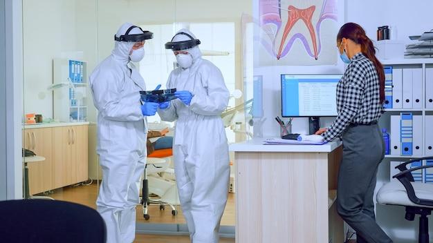 Medici di ortodonzia con visiera e tuta in dpi che discutono alla reception dei raggi x dei denti mentre il paziente aspetta durante la pandemia globale. concetto di nuova normale visita dal dentista nell'epidemia di coronavirus.