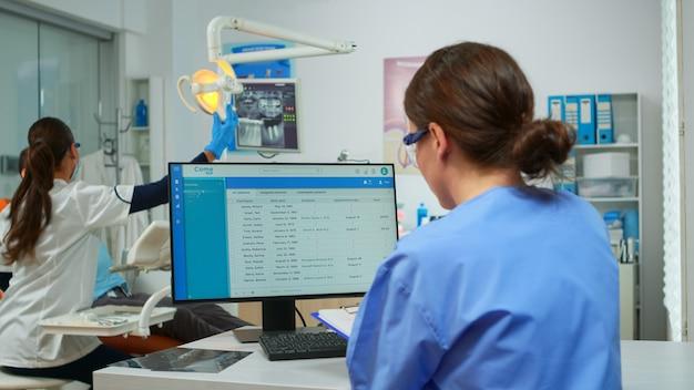 Assistente ortodontista che prende appunti sugli appunti, controlla gli appuntamenti, mentre medico dentista specialista con maschera facciale esamina il paziente con mal di denti seduto sulla sedia stomatologica.