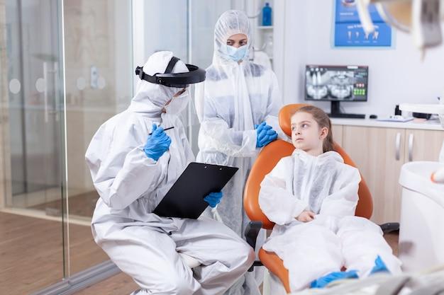 Ortodontista che spiega il trattamento della cavità al genitore e alla bambina vestiti con tuta protettiva contro il coronavirus. stomatologo durante il covid19 che indossa una tuta in dpi facendo la procedura dei denti del bambino seduto