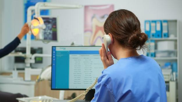 Infermiera ortodontista che parla al telefono facendo appuntamenti dal dentista in un moderno ufficio attrezzato, mentre il dentista specialista con maschera facciale sta esaminando il paziente con mal di denti seduto su una sedia stomatologica.