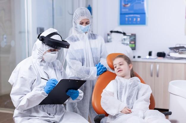 Trattamento di scrittura specialistico ortodontista vestito con tuta durante l'epidemia di coronavirus e consultazione dei bambini. stomatologo durante il covid19 che indossa una tuta in dpi facendo la procedura dei denti del bambino s