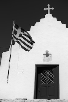 Chiesa ortodossa con bandiera greca, isola di mykonos, grecia. fotografia di architettura in bianco e nero