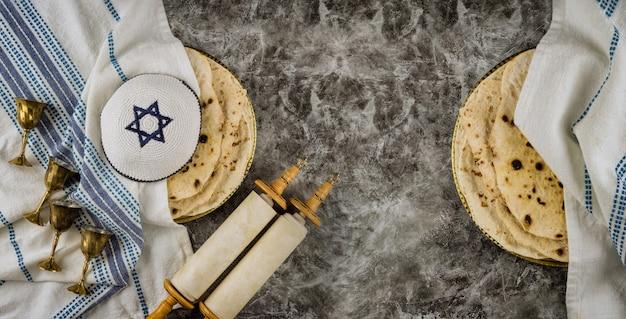 Simboli della famiglia ebrea ortodossa con tazza di vino matzah kosher, festa di pasqua ebraica tradizionale su pergamene sacre torah