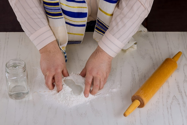 Uomo ebreo ortodosso prepara matzah kosher piatto fatto a mano per la cottura