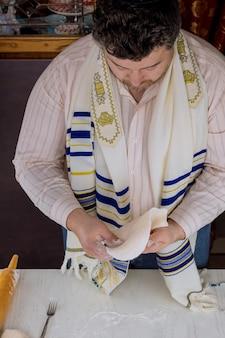 Ebrei ortodossi che arrotolano la pasta per matzos per la pasqua ebraica per metterla in forno per il giorno delle festività ebraiche