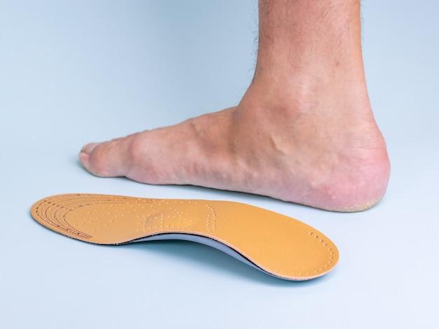Soletta ortopedica sulla gamba destra e sulla gamba di un uomo con segni di piedi piatti su sfondo blu.