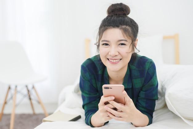 Ortrait di bella donna asiatica sul letto bianco mentre utilizzare smartphone con attraente sorridente