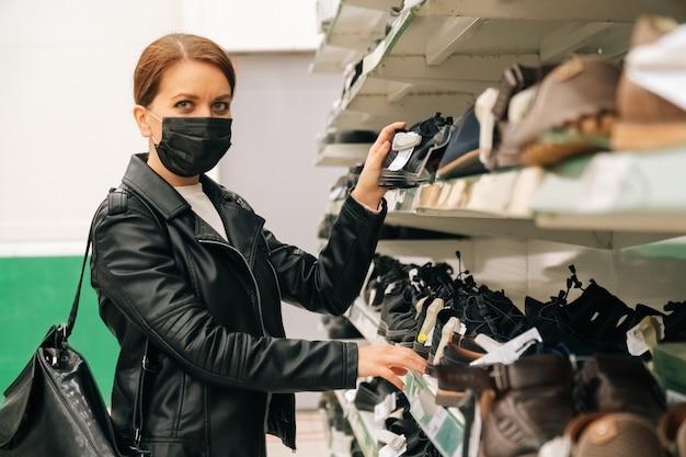 La giovane ragazza caucasica di ortrait in una maschera nera medica sceglie i vestiti, prodotti delle scarpe nel supermercato. il concetto di distanza sociale e