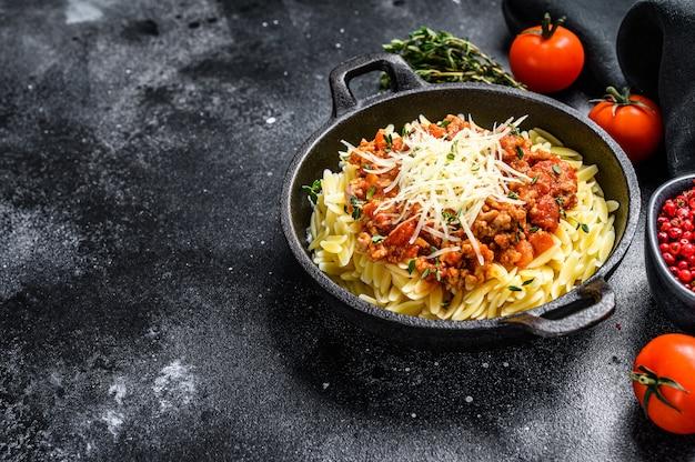 Orzo, risone con ragù alla bolognese e carne macinata sul tavolo nero