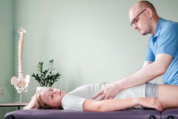 Osteopata che rilascia il diaframma di una paziente, massaggio di rilascio della gabbia toracica, rilassamento dei muscoli respiratori