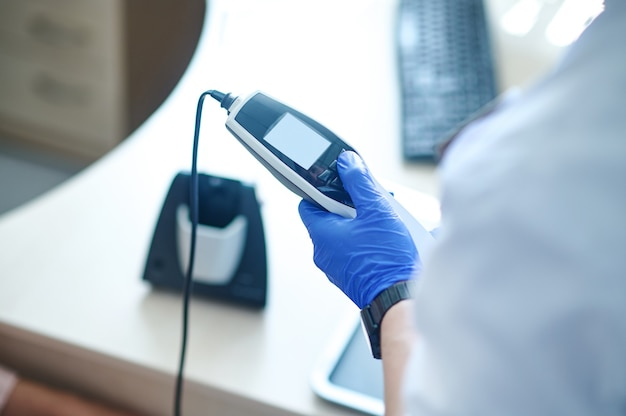 Otorinolaringoiatra che prepara l'attrezzatura per un test di audiometria