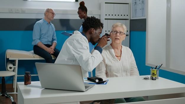 Otologo che fa la consultazione dell'orecchio per il paziente anziano