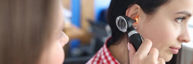 Medico otorinolaringoiatra che diagnostica problemi di udito di una giovane donna che utilizza l'otoscopio
