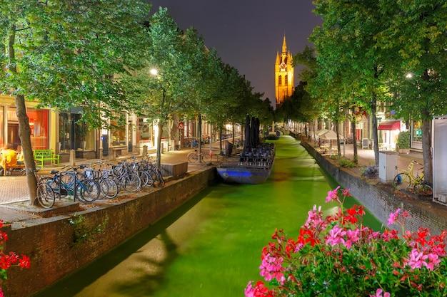 Oude delft canal e torre pendente del gotico protestante oude kerk chiesa di notte, delft, olanda, paesi bassi