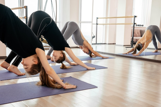 Giovani donne in forma facendo esercizio di posa di yoga per cani su stuoie in palestra. concetto di sport.