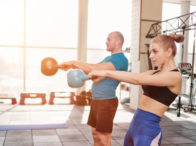 Ðallenamento funzionale in coppia. uomo sportivo e donna in forma facendo esercizio con kettlebell in palestra