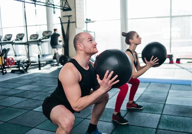 Addestramento funzionale doppio. l'uomo sportivo e la donna adatta si esercitano con la palla medica in palestra