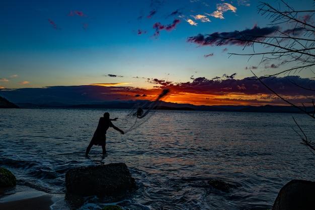 Il nostro pesce quotidiano. silhouette di un pescatore che getta la rete da pesca, chiamata