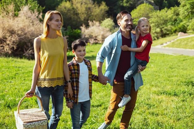 Il nostro giorno libero. soddisfatto uomo dai capelli scuri che tiene sua figlia mentre trascorre del tempo con la sua famiglia