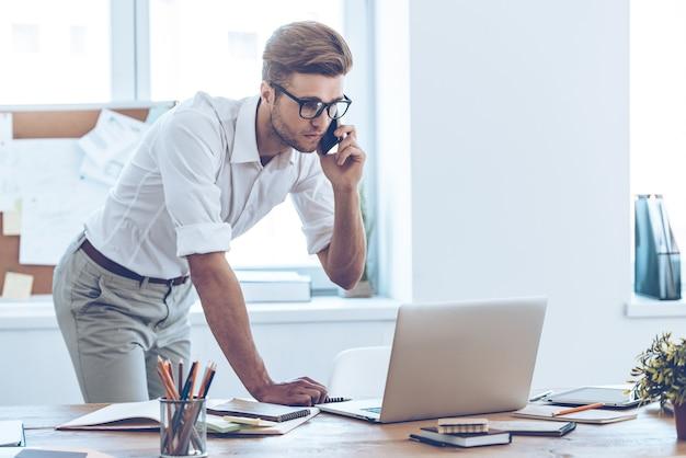 Il nostro incontro è in ritardo! giovane bell'uomo che usa il suo laptop e parla al cellulare mentre si appoggia al suo posto di lavoro