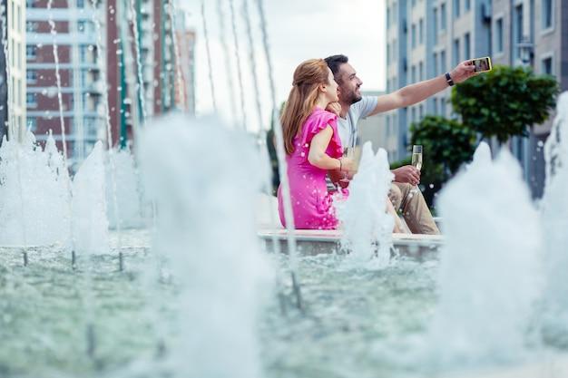 La nostra memoria. gioiosa coppia felice seduta vicino alla fontana mentre si scattano selfie insieme