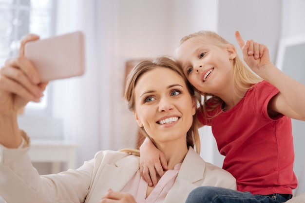 La nostra foto. felice positiva bella madre e figlia sorridendo ed esaminando la fotocamera mentre si prende un selfie