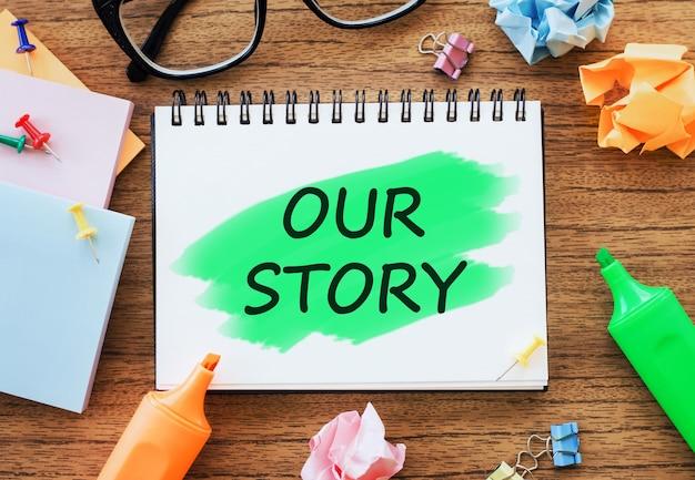 La nostra storia testo sul blocco note sul tavolo di legno con diario aperto, bicchieri, pennarelli, carta stropicciata e graffette