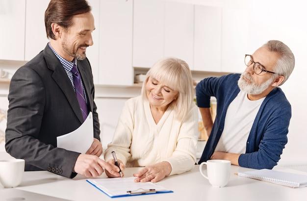 Il nostro utile investimento. fiducioso e carismatico agente immobiliare esperto che incontra una coppia di clienti anziani mentre lavora e aiuta i clienti con la scelta