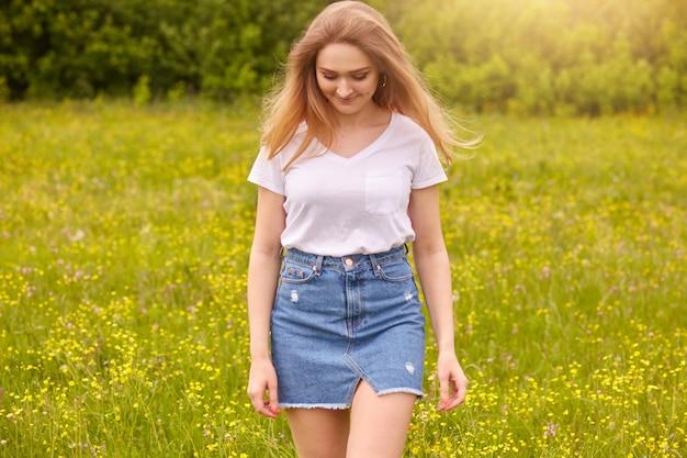 Colpo di ourdoor di giovane bella ragazza caucasica in maglietta bianca e gonna di jeans blu in posa contro il tramonto nel prato, guardando in basso, attraente femmina guardando in basso. concetto di stile di vita e felicità.