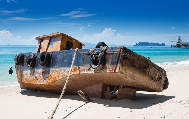 Fuori fuoco della vecchia e arrugginita barca d'epoca sulla spiaggia con illuminazione solare all'aperto.