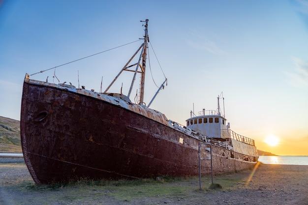 Una baleniera fuori mano che è naufragata sulla spiaggia di latrabjarg durante il tramonto.