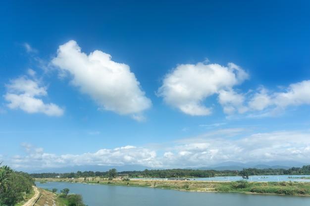 Nuvole bianche all'aperto del cielo blu e paesaggio rurale