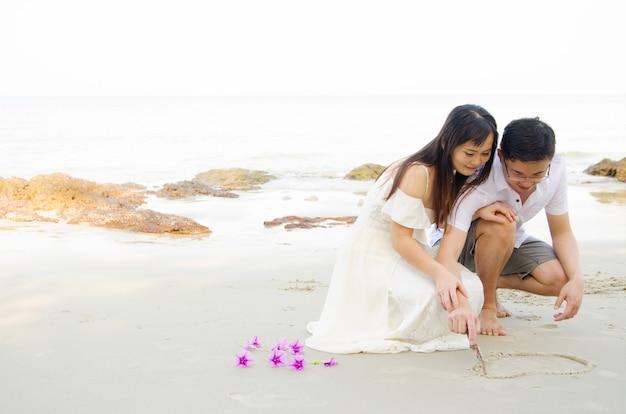 All'aperto sposa e sposo sulla spiaggia di sera.