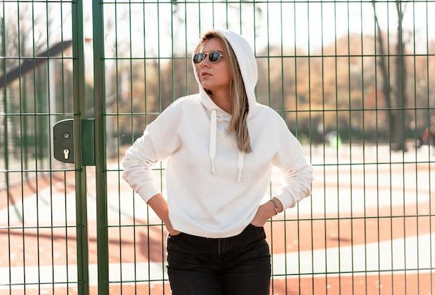 Ritratto alto vicino all'aperto di giovane bella donna con capelli lunghi in occhiali da sole, vestito con un maglione con cappuccio bianco, vicino al campo sportivo. cultura giovanile passatempo estivo