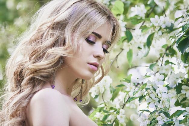 Moda all'aperto bella giovane donna circondata da fiori lilla estate. cespuglio di lillà del fiore di primavera. ritratto di una ragazza bionda
