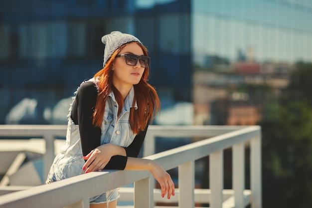 Ritratto di stile di vita di moda all'aperto di bella ragazza, che indossa in fondo urbano hipster swag grunge stile. concetto di città maschiaccio