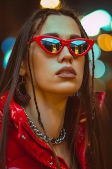 Ritratto di moda all'aperto di giovane donna glamour con i capelli intrecciati indossa piumino rosso e occhiali da sole rossi di moda sui lampioni al neon