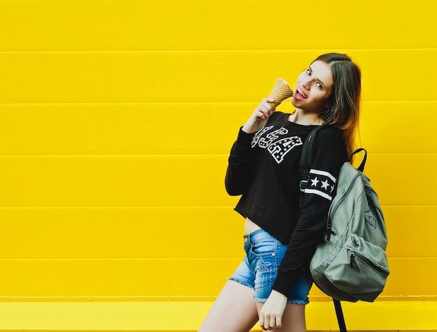 Ritratto di moda all'aperto di giovane ragazza con gelato su sfondo muro giallo