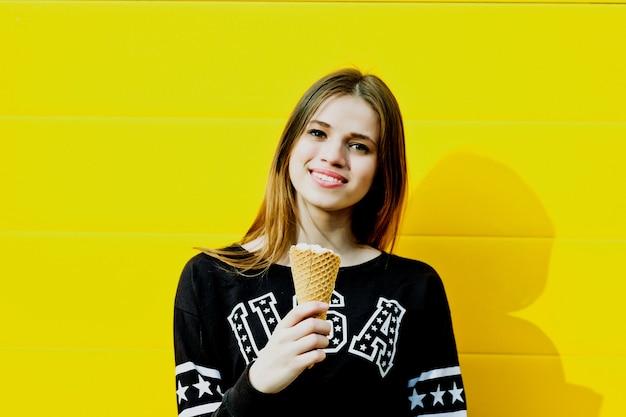 Ritratto di moda all'aperto di giovane ragazza hipster con gelato su sfondo muro giallo