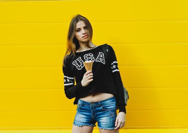 Ritratto di moda all'aperto di giovane ragazza hipster con gelato sul muro giallo muro