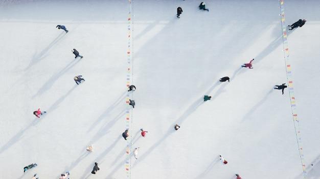Pista di pattinaggio sul ghiaccio all'aperto con persone che cavalcano in una giornata invernale. vista aerea dal drone.