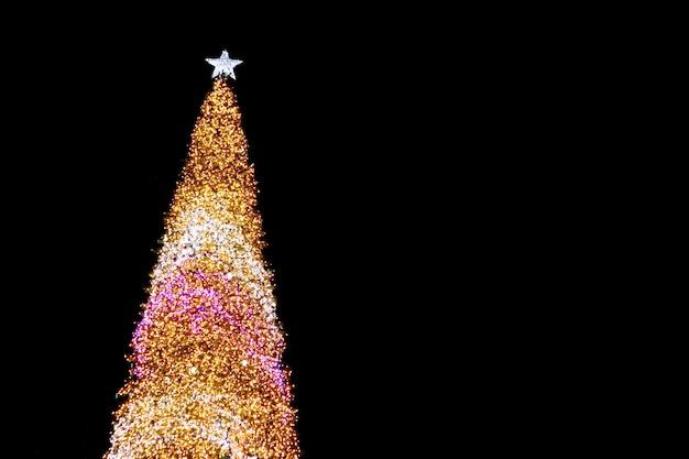 Albero di natale gigante illuminato a led per esterni contro il cielo notturno scuro
