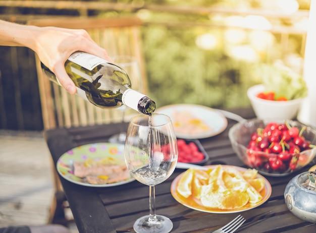 Pranzo all'aperto con vino bianco, frutta, piatti. vacanze estive