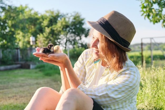 Outdoor donna matura contadina che tiene in mano due piccoli polli neonati, stile rustico country, golden hour