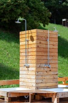 Doccia esterna moderna realizzata con pannelli in legno marrone vicino alla piscina. igiene del corpo prima di nuotare nell'acqua della piscina.