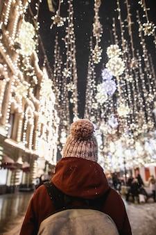 Ritratto notturno all'aperto di giovane donna alla moda con il cappello invernale con vista posteriore del pompon. effetto magico della nevicata. illuminazione stradale notturna a mosca.
