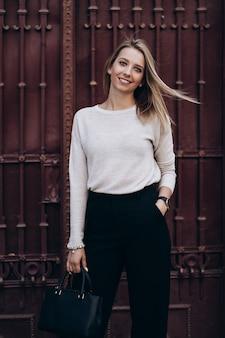 Foto all'aperto di signora bionda in posa sullo sfondo di architettura nel giorno di autunno. close up fashion street style portrait. indossando pantaloni casual scuri, maglione cremoso e cappotto o giacca grigio. concetto di moda.