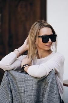 Foto all'aperto di signora bionda in posa sullo sfondo di architettura nel giorno di autunno. ritratto di moda street style. indossa pantaloni scuri casual e maglione cremoso e occhiali da sole. concetto di moda.
